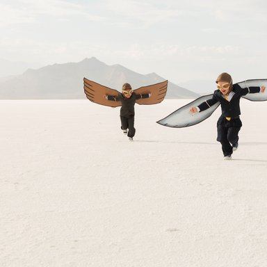 Young Business Boys Wearing Cardboard Wings Are Flying