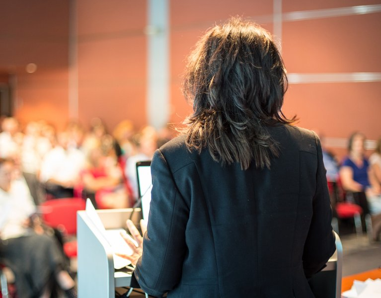 Female public speaker giving talk at Business Event.