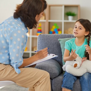 Happy little girl telling story to child psychologist during therapy session in cozy modern office