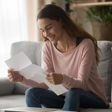 Happy woman read letter with loan approval sit on sofa