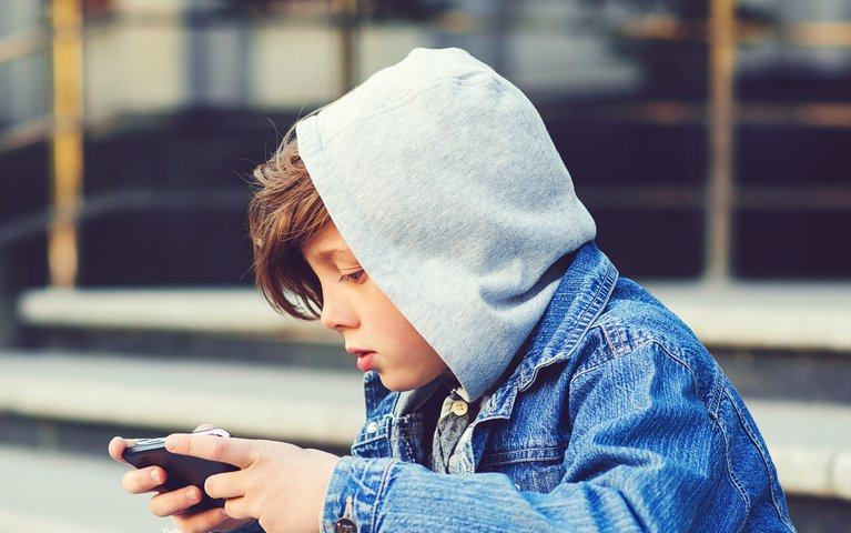 Schoolboy with smartphone sitting on stairs after school. Technology, education and lifestyle concept. Kid texting message or playing game outdoors